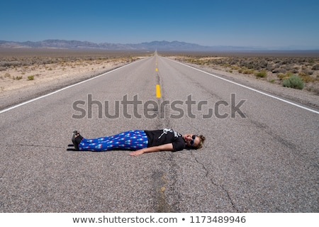woman with bicycle laying on asphalt Stock photo © LightFieldStudios