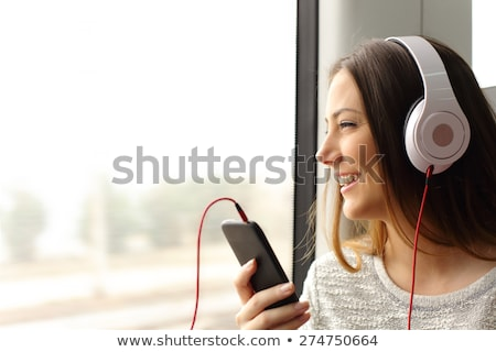 Woman at window, listening to music Stock photo © IS2