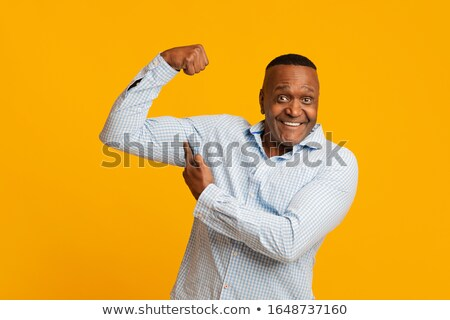 cheerful afro american sports man showing his biceps stock photo © deandrobot