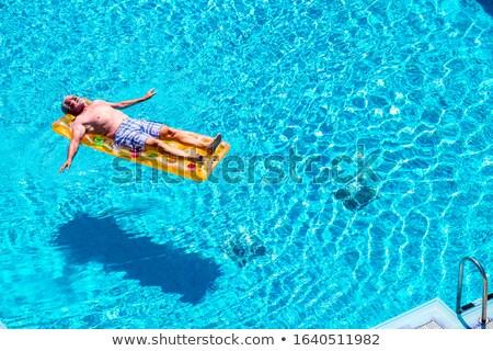 homem · flutuante · inflável · colchão · piscina · verão - foto stock © is2