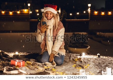 emotional excited young woman sitting outdoors in evening in christmas hat using mobile phone stock photo © deandrobot