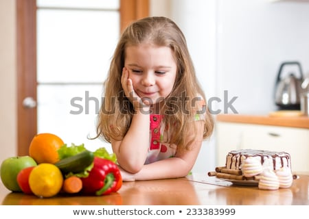 kid choosing between healthy vegetables and tasty sweets Stock photo © Lopolo