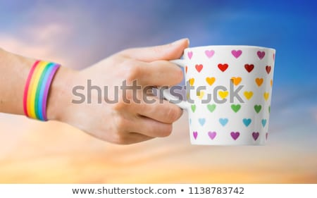 Stock fotó: Hand With Cup Of Cacao And Gay Awareness Wristband