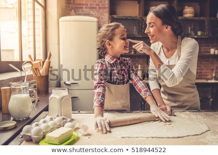 happy mother and daughter baking muffins at home stock photo © dolgachov