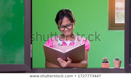 Black hair little girl with glasses holding books by the wall Stock photo © boggy