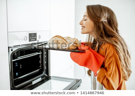 smiling woman holding bread stock photo © kzenon