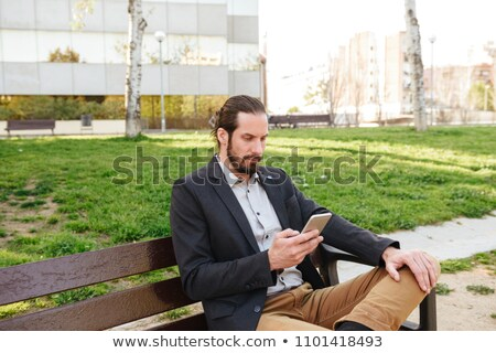 Photo of smart attractive man 30s in businesslike suit holding a Stock photo © deandrobot