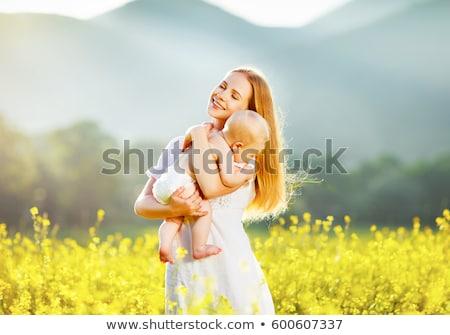 Boldog család anya baba ölel legelő sárga virágok Stock fotó © ElenaBatkova