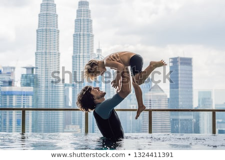 Father and son in outdoor swimming pool with city view in blue sky Stock photo © galitskaya