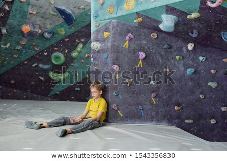 Youthful boy looking at his hands while sitting on mat by climbing equipment Stock photo © pressmaster