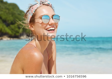 Beautiful woman on a sandy beach in sunglasses on background of ocean Stock photo © ElenaBatkova