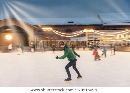 Cheerful bearded man spends Christmas time on majestic ice rink decorated with lights, skates on ice Stock photo © vkstudio