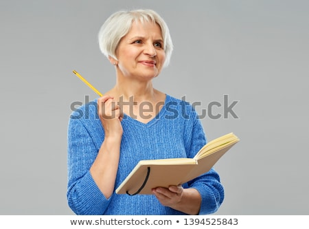 senior woman with pencil and diary or notebook Stock photo © dolgachov