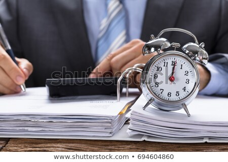 Businessman Calculating Invoice With Alarm Clock Stock photo © AndreyPopov