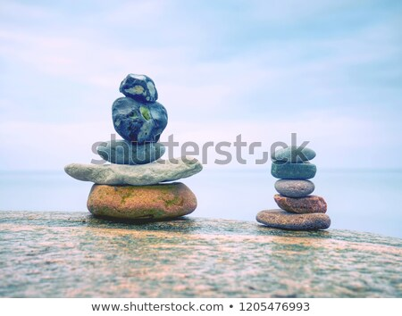 Pebbles stack in peaceful evening with smooth ocean background.  Stock photo © Ansonstock