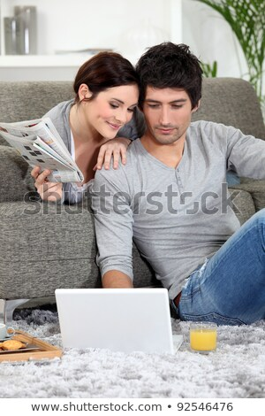 Couple sat on couch with newspaper and laptop Stock photo © photography33