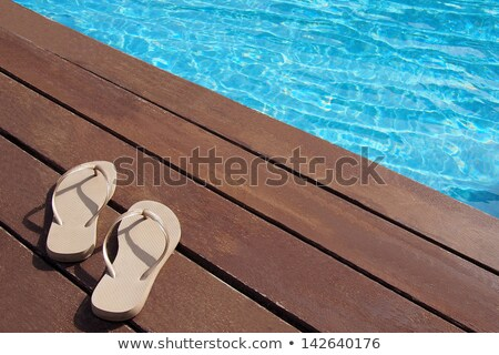 Pair of slippers by a swimming pool Stock photo © stockyimages