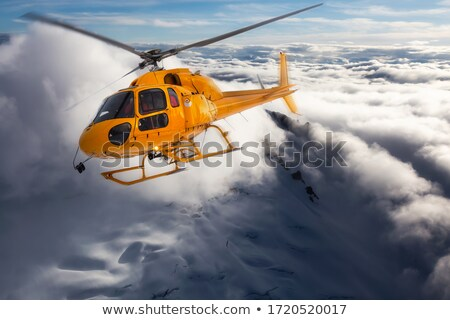 Helicopter in cloudy sky and winter mountains Stock photo © BSANI