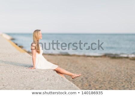 ブロンド 女性 座って 石の壁 ビーチ 長い ストックフォト © dash