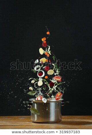 Foto d'archivio: Fresh Vegetables Falling Into A Stainless Steel Casserole