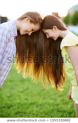 mother stand on the grass, daughter  hang on it Stock photo © Paha_L