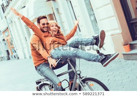 Happy young woman riding bike on autumn day stock photo © cienpies