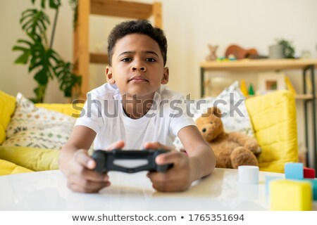 Happy boy with teddy bear playing games holding joystick Stock photo © deandrobot
