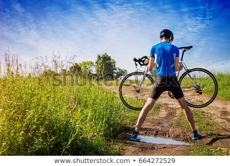 Man carrying cycle across field Stock photo © IS2