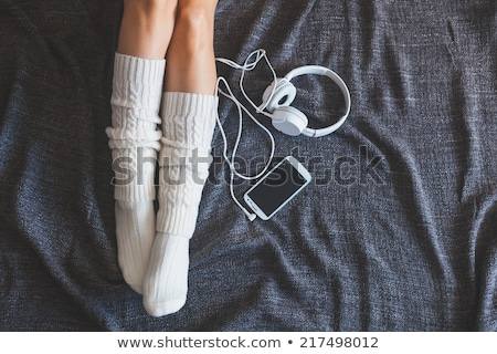 woman with smartphone and headphones in bed stock photo © dolgachov