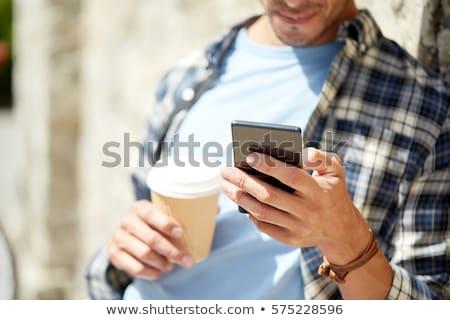 Homme smartphone mur de pierre rue de la ville loisirs technologie Photo stock © dolgachov