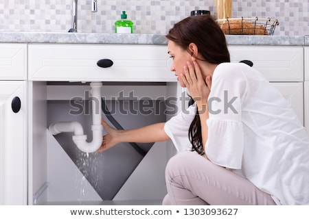 woman trying to stop water leakage from sink pipe stock photo © andreypopov