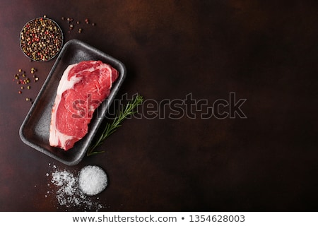 Raw sirloin beef steak in plastic tray with salt and pepper and fresh rosemary on rusty background. Stock photo © DenisMArt