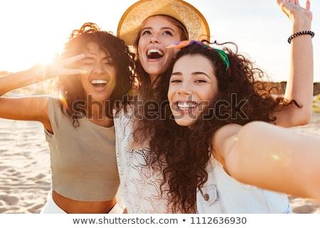 Foto d'archivio: Group Of Smiling Women Taking Selfie On Beach