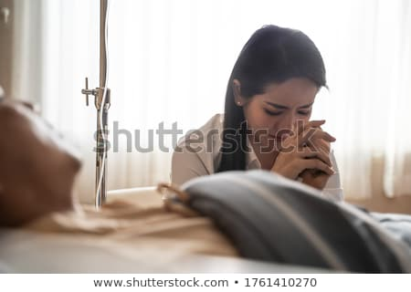 Stock photo: Husband looking after wife in hospital