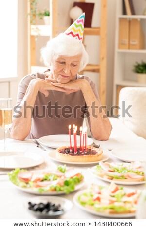 Emeryturę kobiet patrząc palenie świece Zdjęcia stock © pressmaster