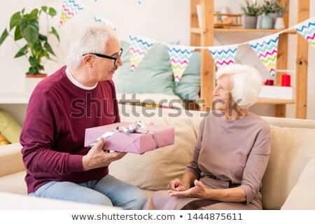 Senior man giving packed present to his wife at home party Stock photo © pressmaster