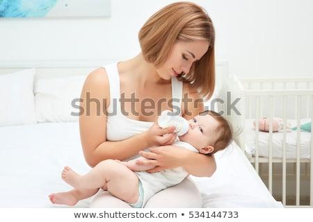 Сток-фото: Woman Feeding Baby On Bed