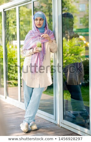 Pretty young serene female in casualwear and hijab having drink on terrace Stock photo © pressmaster