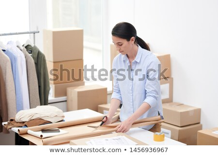 Young manager of online shop of casualwear cutting wrap paper Stock photo © pressmaster