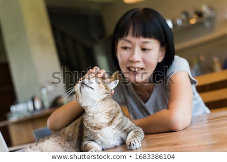 Woman stroking the head of her tabby cat Stock photo © Giulio_Fornasar