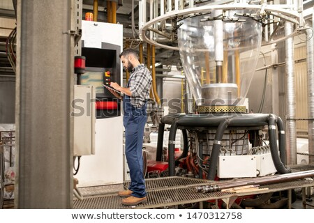 busy young engineer of factory with tablet standing by control panel stock photo © pressmaster
