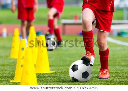 Children training football dribbling in a field Stock photo © matimix