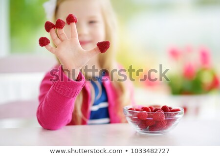 Cute fille manger framboises doigts souriant Photo stock © lichtmeister