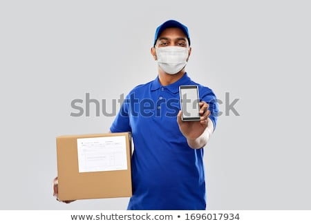 indian delivery man with smartphone and parcel box Stock photo © dolgachov