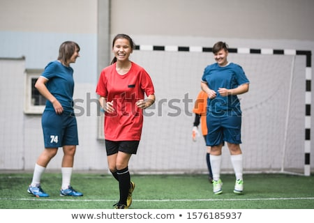 Laughing active girl in sports uniform running down green football field Stock photo © pressmaster