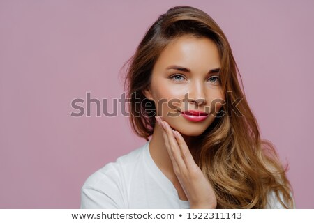 People, beauty and feminity concept. Lovely calm attractive lady with appealing look, keeps palm on  Stock photo © vkstudio