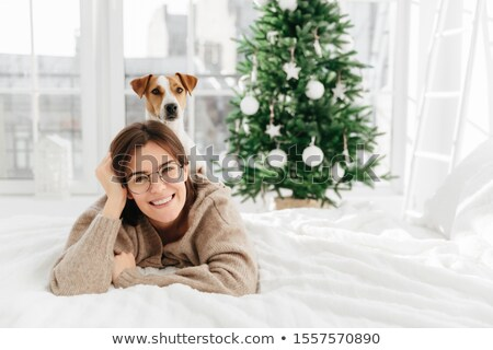 Pretty cheerful woman wears big optical round glasses, lies on bed, her dog poses on back, have fun  Stock photo © vkstudio