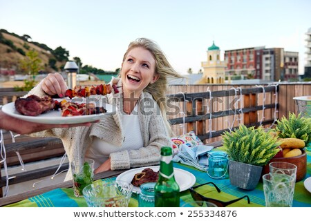man grilling meat on bbq at rooftop party Stock photo © dolgachov
