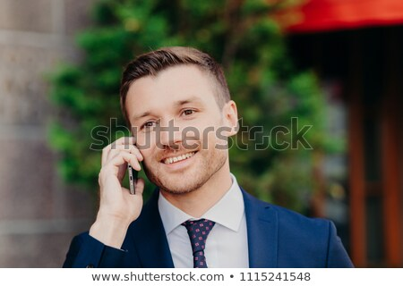 Successful male office worker has conversation about business affairs via cell phone, dressed in for Stock photo © vkstudio