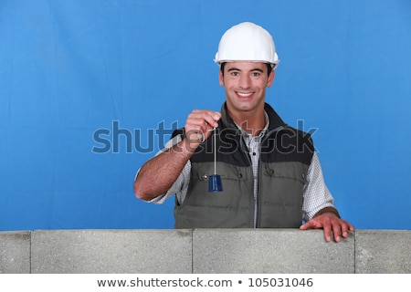 portrait of young bricklayer posing near unfinished concrete wall holding bell Stock photo © photography33